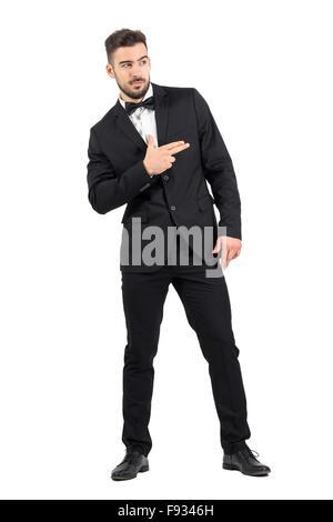 Lustige Geheimagent mit Finger gewehr Hand Geste wegsehen. Ganzkörper-Länge-Porträt über weiße Studio-Hintergrund - Stockfoto