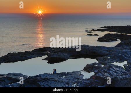 Sonnenuntergang in Cornwall an der Treyarnon Bay England UK an einem Sommerabend mit Mädchen sitzen auf den Felsen, - Stockfoto