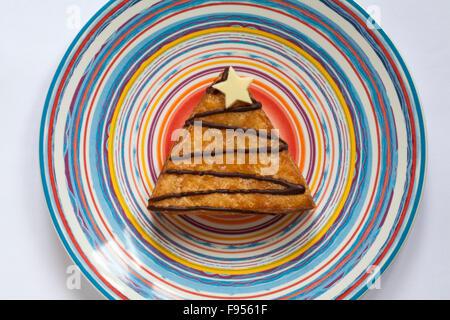& S M Weihnachtsbaum Yum Yums iced Donut gefüllt mit Toffee-Sauce auf gestreiften Teller - Stockfoto