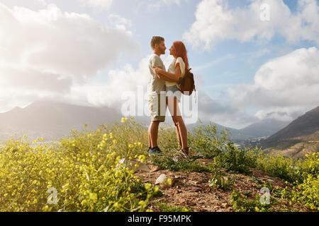 Porträt von verliebten Paar in Umarmung stehend auf einem Hügel. Junger Mann und Frau in der Liebe stehen zusammen - Stockfoto