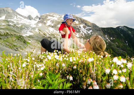 Eine junge Mutter und ihr Kind in Blumenwiesen auf Alpen Alturas liegen in der Nähe von New Denver, British Columbia - Stockfoto
