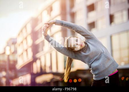 Junge weibliche Läufer in hoody ist vor dem Lauf in der Stadtstraße stretching. - Stockfoto