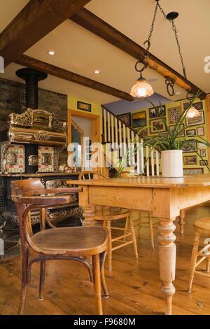 Holztisch mit Stühlen und einem antiken Royal Modell Holz Kochen Herd im Esszimmer im Landhausstil cottage - Stockfoto