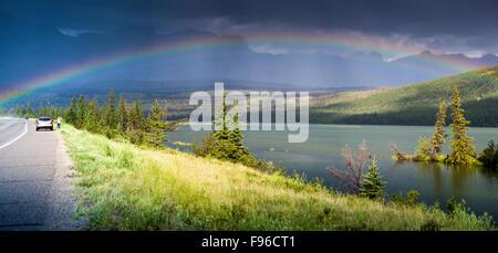 Ein Tourist fotografiert einen Regenbogen über Talbot Lake und den Yellowhead Highway in Jasper Nationalpark, Alberta, - Stockfoto