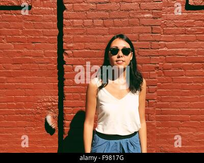 Porträt der schönen jungen Frau stehend gegen die roten Backsteinmauer