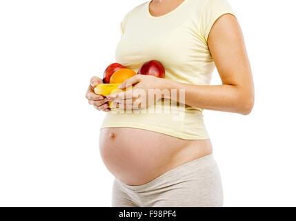 Unkenntlich schwangere Frau mit Obst, isoliert auf weißem Hintergrund - Stockfoto