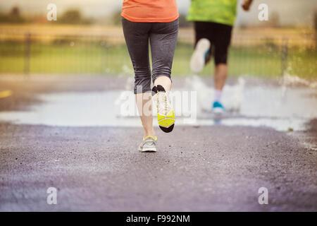 Junges Paar laufen auf Asphalt Sportplatz bei Regenwetter. Details der Beine und Sportschuhe in Pfützen planschen. - Stockfoto