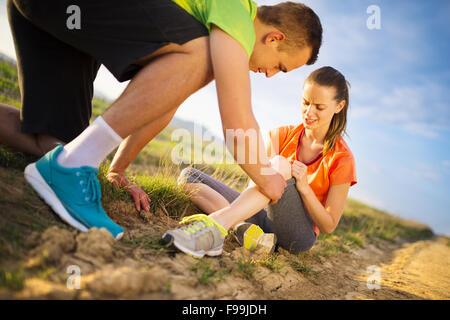 Verletzungen - Sport Frau mit verletzten Knie Hilfe von Mann ihr Knie berühren. - Stockfoto
