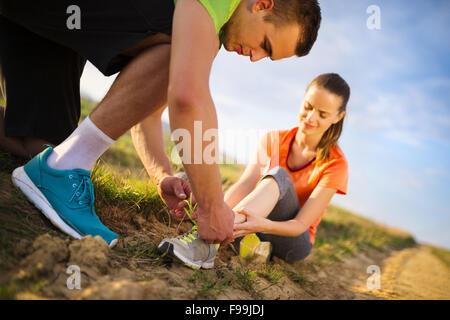 Verletzungen - Sport Frau mit verdrehten verstauchten Hilfe bekommen von Mann berühren ihren Knöchel. - Stockfoto
