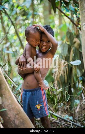 Der junge Aborigines Orang Asil hält sein schreiendes Baby Bruder in seine Arme, Naturvolk, tropischer Regenwald - Stockfoto