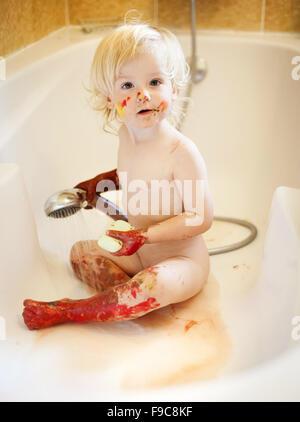 Nettes Kind waschen Körper voller Farbe. - Stockfoto