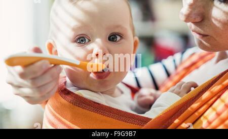 Junge Mutter füttert ihre kleine Tochter, die sie in einem Tragetuch hat - Stockfoto