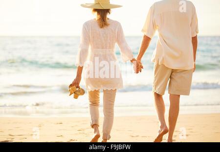 Glückliche romantische mittleren gealterten paar schönen Sonnenuntergang genießen Strandspaziergang Hand in Hand - Stockfoto
