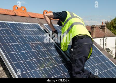 Arbeiter installieren Photovoltaik-Solarzellen auf das Schieferdach ein viktorianisches Haus in London, England. - Stockfoto