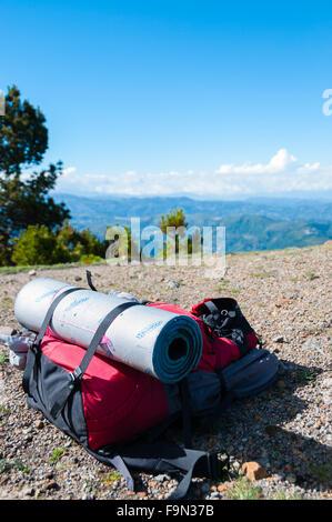 Rot Rucksack mit Isomatte legt auf felsigen Boden vor Berg Tajamulco und blauer Himmel mit Wolken - Stockfoto