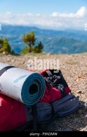 Closeup rot Rucksack mit Isomatte legt auf felsigen Boden vor Berg Tajamulco und blauer Himmel mit Wolken - Stockfoto