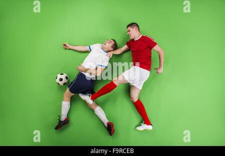 Zwei Fußballspieler kämpfen für einen Ball. Studio auf einem grünen Hintergrund gedreht. - Stockfoto