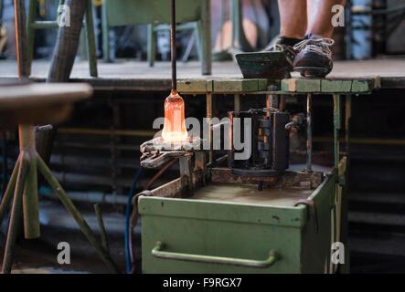 Glasschmelze, glühend heiß, rot wird in eine Form der traditionellen Glasblasen-Manufaktur in Hergiswil, Schweiz - Stockfoto