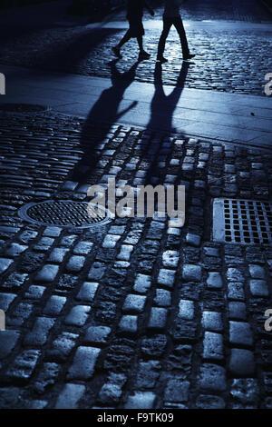 Zwei junge Menschen wandern in blaue Nacht Schatten auf gepflasterten Straße - Stockfoto