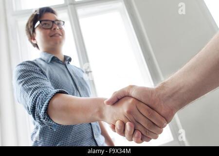 Zwei junge Berufstätige, die Hände schütteln - Stockfoto