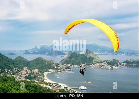 Leuchtend gelbe Hängegleiter fliegen über die bergige Skyline Skyline der Stadt vom Parque da Cidade Park in Niteroi, - Stockfoto