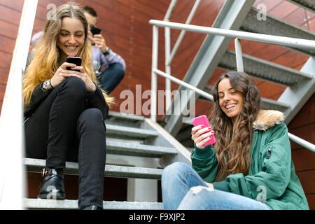 Drei Freunde hanging around mit Handys oudoors - Stockfoto