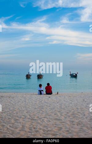 Wenige Touristen sitzen auf weißem Sand, einen ruhiger Ozean teilen anzeigen Moment am Strand vor einem ruhigen - Stockfoto