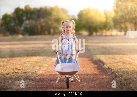 kleine Mädchen spielen mit einer Schubkarre - Stockfoto