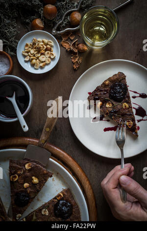 Person Essen ein Stück einer festlichen Mittelmeer Kastanien Mehl Kuchen am Set Holztisch mit Zutaten, Weihnachtsdekoration, - Stockfoto