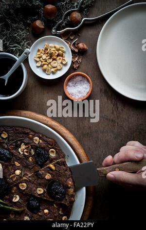 Person auf einer festlichen Mittelmeer Kastanien Mehl Kuchen in weiße Schale schneiden setzen Holztisch mit Zutaten - Stockfoto