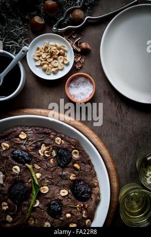 Festliche Mittelmeer Kastanien Mehl Kuchen in weiße Schale auf Set Holztisch mit Zutaten, Weihnachtsdekoration und - Stockfoto
