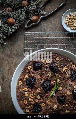 Festliche Mittelmeer Kastanien Mehl Kuchen in weißen Schale auf Rack-Kühlung über hölzerne Tischplatte. Ansicht - Stockfoto