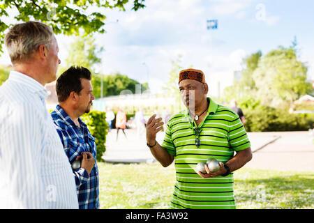 Freunde diskutieren beim Spielen Boule im park - Stockfoto