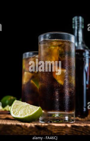 Hausgemachte Cuba Libre mit frischer Limette, brauner Rum und crushed Ice auf einem alten Holztisch - Stockfoto