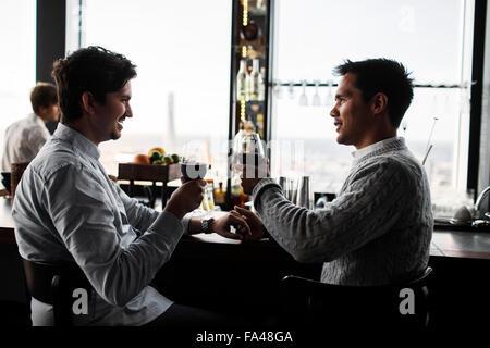 Gay paar Toasten mit Rotwein am Tisch im Restaurant Sky bar - Stockfoto