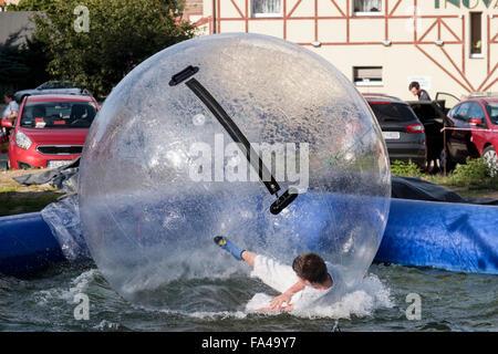 Junge Spaß Zorbing in einer aufblasbaren Kugel Blase auf einer Lache des Wassers. Polanica-Zdrój, Glatz, Polen, - Stockfoto