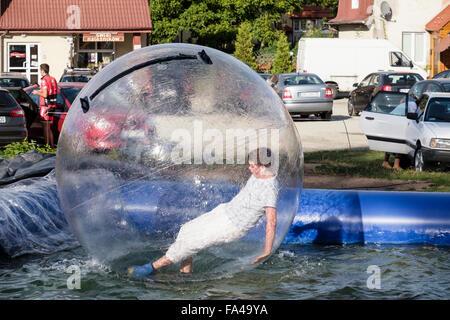 Junge mit Spaß in einer aufblasbaren Zorb-Ball-Blase auf einen Pool von Wasser nach hinten fallen. Polanica-Zdrój, - Stockfoto