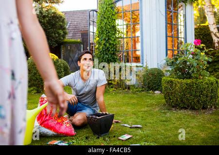 Glücklich reifer Mann im Garten im Hinterhof mit Tochter im Vordergrund - Stockfoto