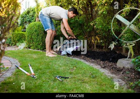 Voller Länge Seitenansicht des reifen Mannes verbreiten Dünger im Garten - Stockfoto