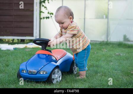 Baby Junge spielt mit seinem Spielzeugauto in Rasen, München, Bayern, Deutschland - Stockfoto
