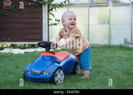Baby Boy mit seinem Spielzeugauto und weinend in Rasen, München, Bayern, Deutschland