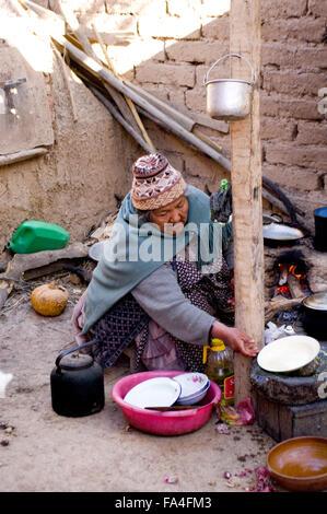 Sonnigen Blick auf eine ältere bolivianischen Frau trägt einen gestrickter Wolle Hut und Kochen Schmutz Etage Küche - Stockfoto