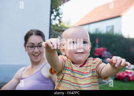 Mutter ist erstaunt über ihr Baby Sohn auf erste Schritte, München, Bayern, Deutschland