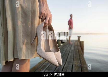 Reifer Mann wartet auf seine Frau am Pier am See, Bayern, Deutschland