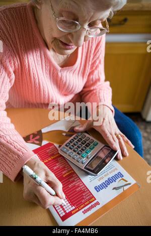 Ältere Frau füllen Sie Details der Ausgaben ein Wochenbudget ausarbeiten, - Stockfoto