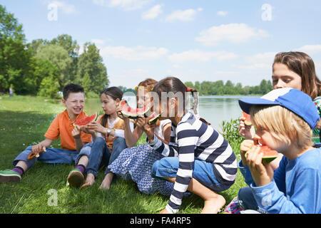 Kinder freuen sich über Scheiben Wassermelone bei Picknick, München, Bayern, Deutschland - Stockfoto