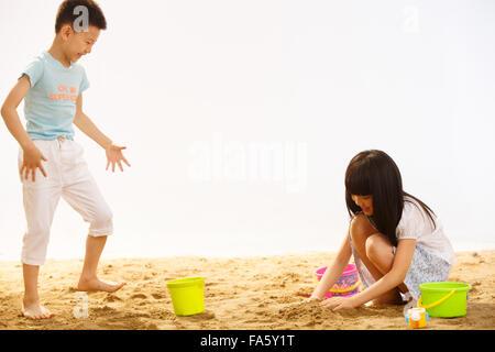 Jungen und Mädchen spielen Sand am Strand - Stockfoto