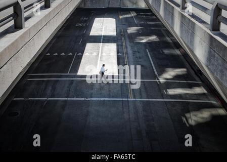 Blick von oben auf eine City-Plaza und zwei Männer, die zu Fuß vom Schatten ins Sonnenlicht. - Stockfoto
