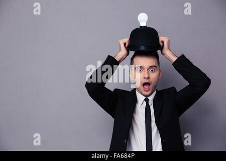 Konzept-Foto eines Geschäftsmannes, eine Vorstellung über den grauen Hintergrund - Stockfoto