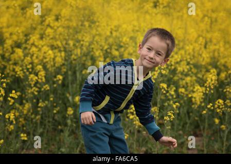 Lächelnde junge Flickschusterei in Raps Feld - Stockfoto